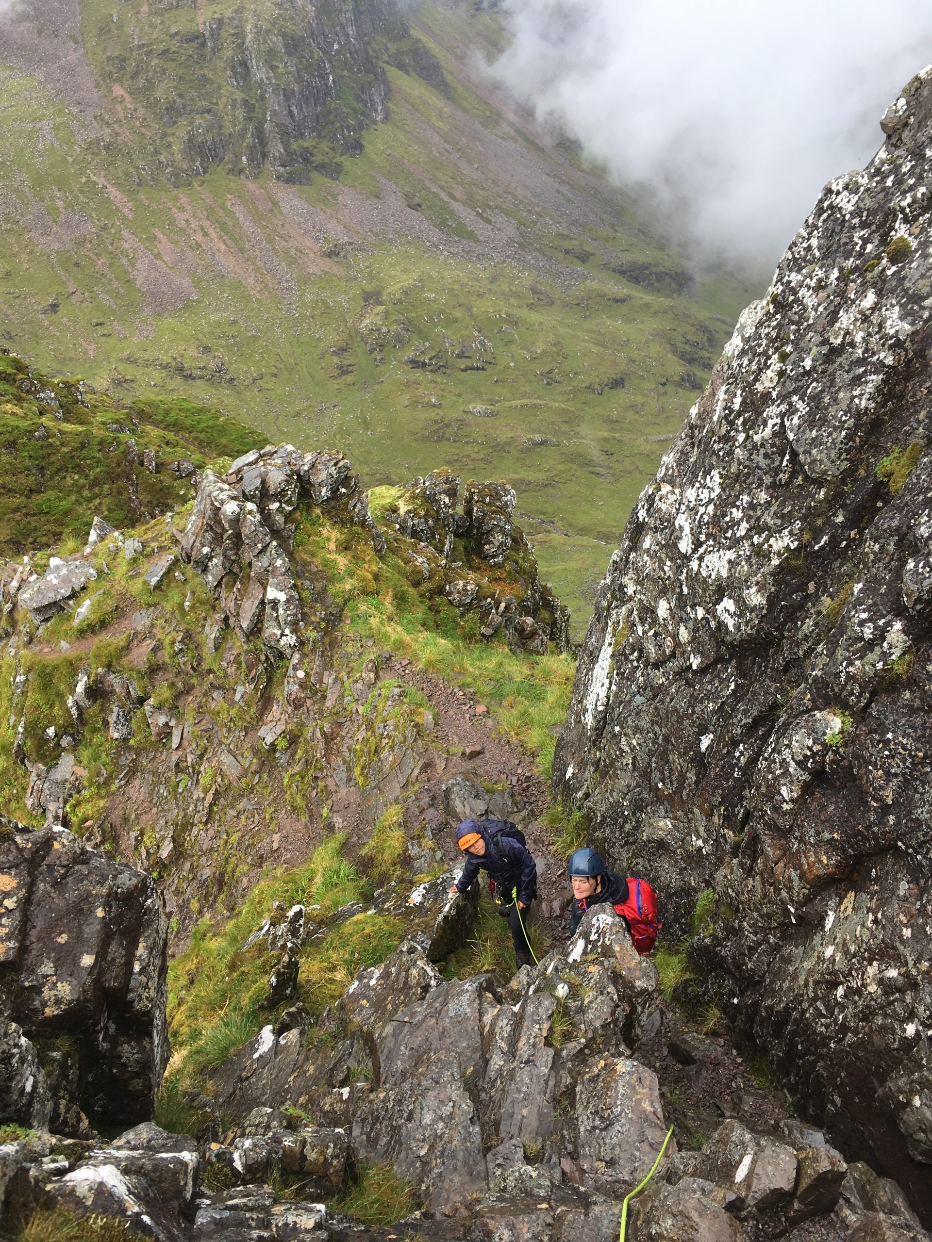 Two climbers wait their turn to move at one of the steeper sections while scrambling the Aonach Eagach Ridge in Glencoe