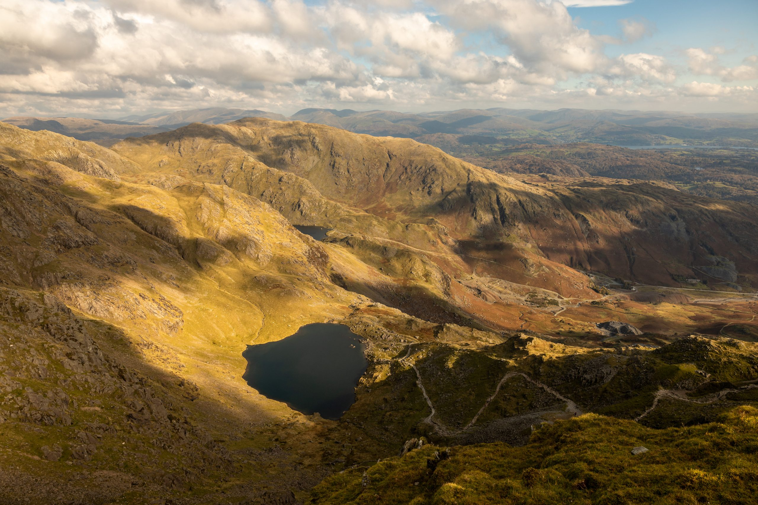 Low Water catches the sun during an autumn guided walk up the Old Man of Coniston in the Lake District