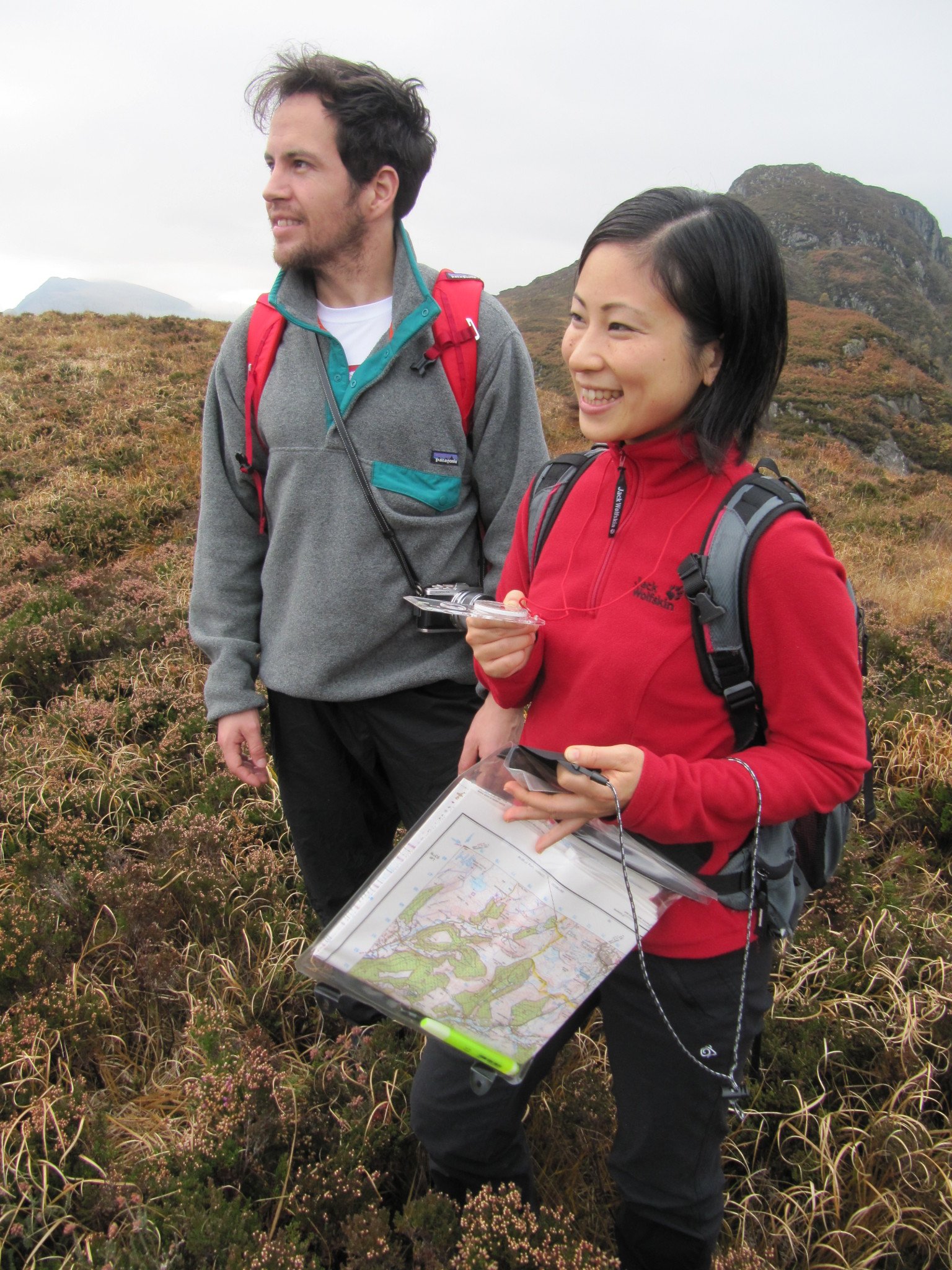 Two students practising taking a compass bearing on a navigation course