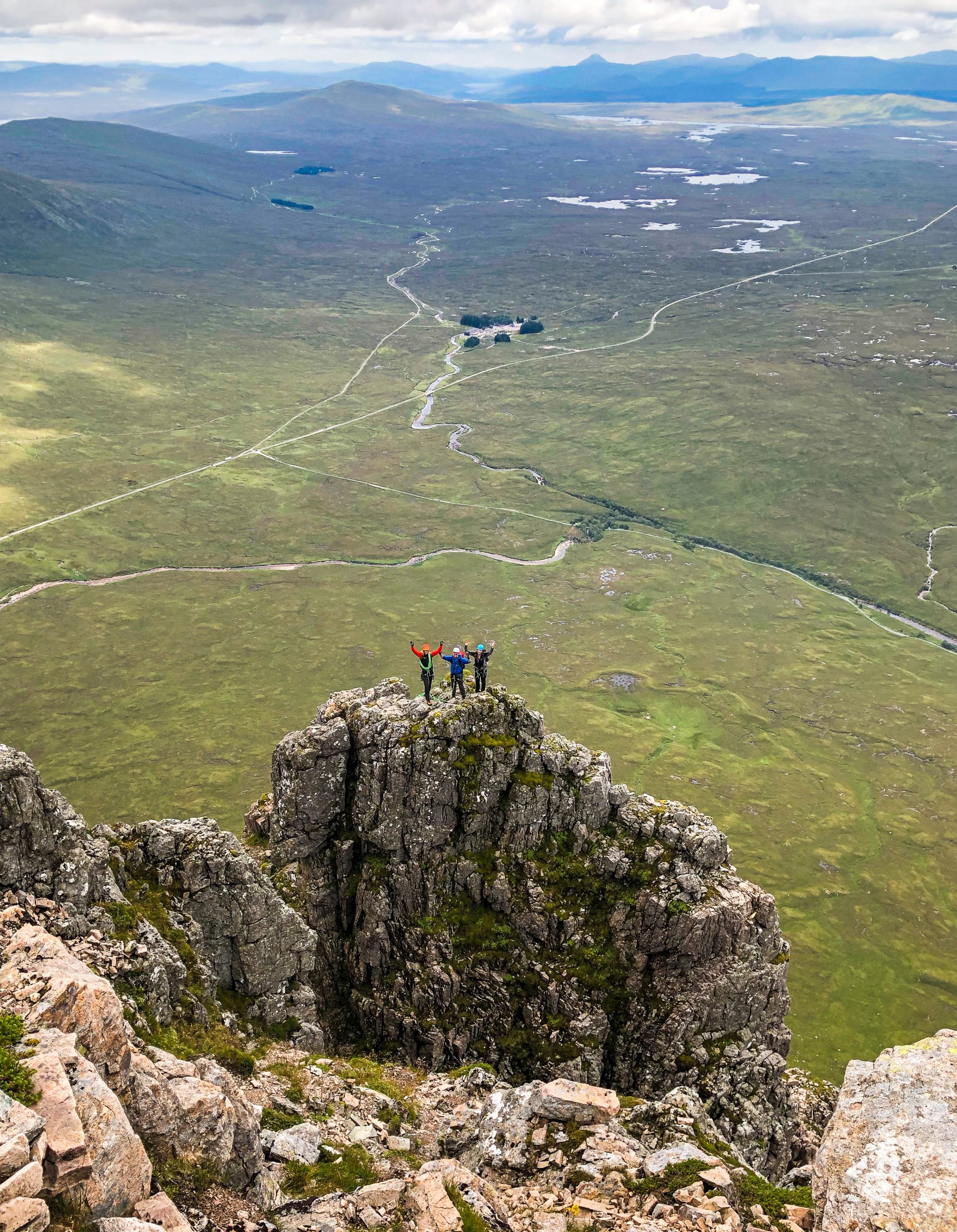 A group wave triumphantly from the top of Crowberry Tower, having scrambled Curved Ridge in Glencoe