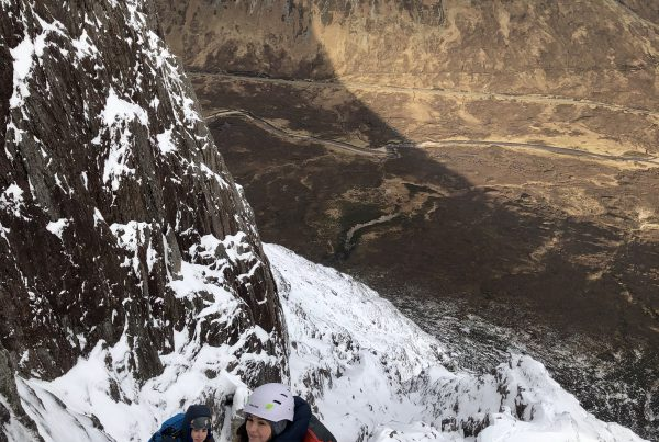 Two climbers making their way up a snowy mountain face on Curved Ridge in Scotland