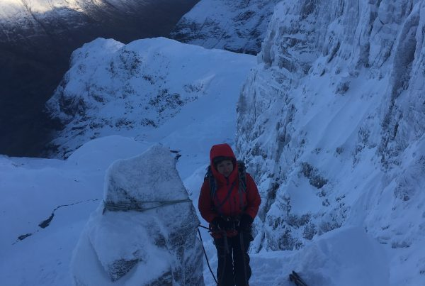 A climber in a red jacket waits at her belay stance at a very narrow section of the ridge on Dorsal Arete in Glencoe