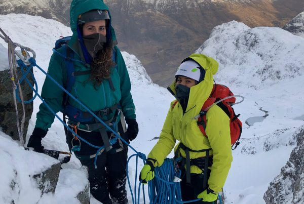 Two climbers at a belay stance high up on Dorsal Arete in Glencoe on a winter mountaineering course