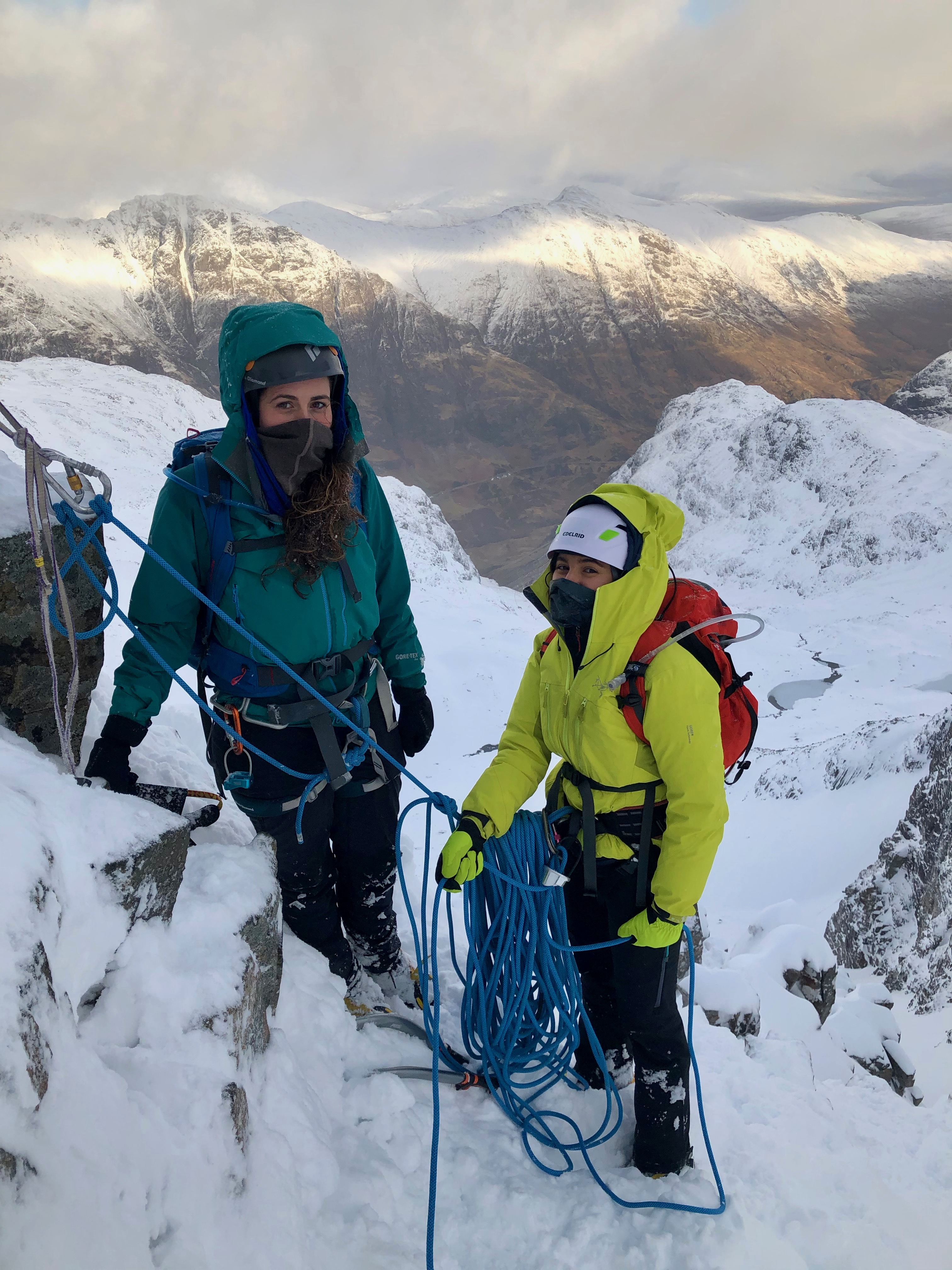 """Two climbers at a belay stance high up on Dorsal Arete in Glencoe on a winter mountaineering course in Scotland"""" width="""
