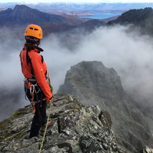 A climber admiring the view from the summit of the Inaccessible Pinnacle, or In Pin, on the Cuillin Ridge on Skye during a mountaineering and rock climbing course