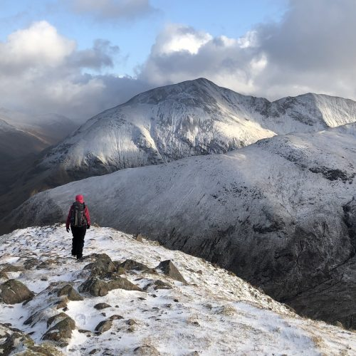 A lone walker stands out against the snowy summits of the Mamores while descending in the afternoon light