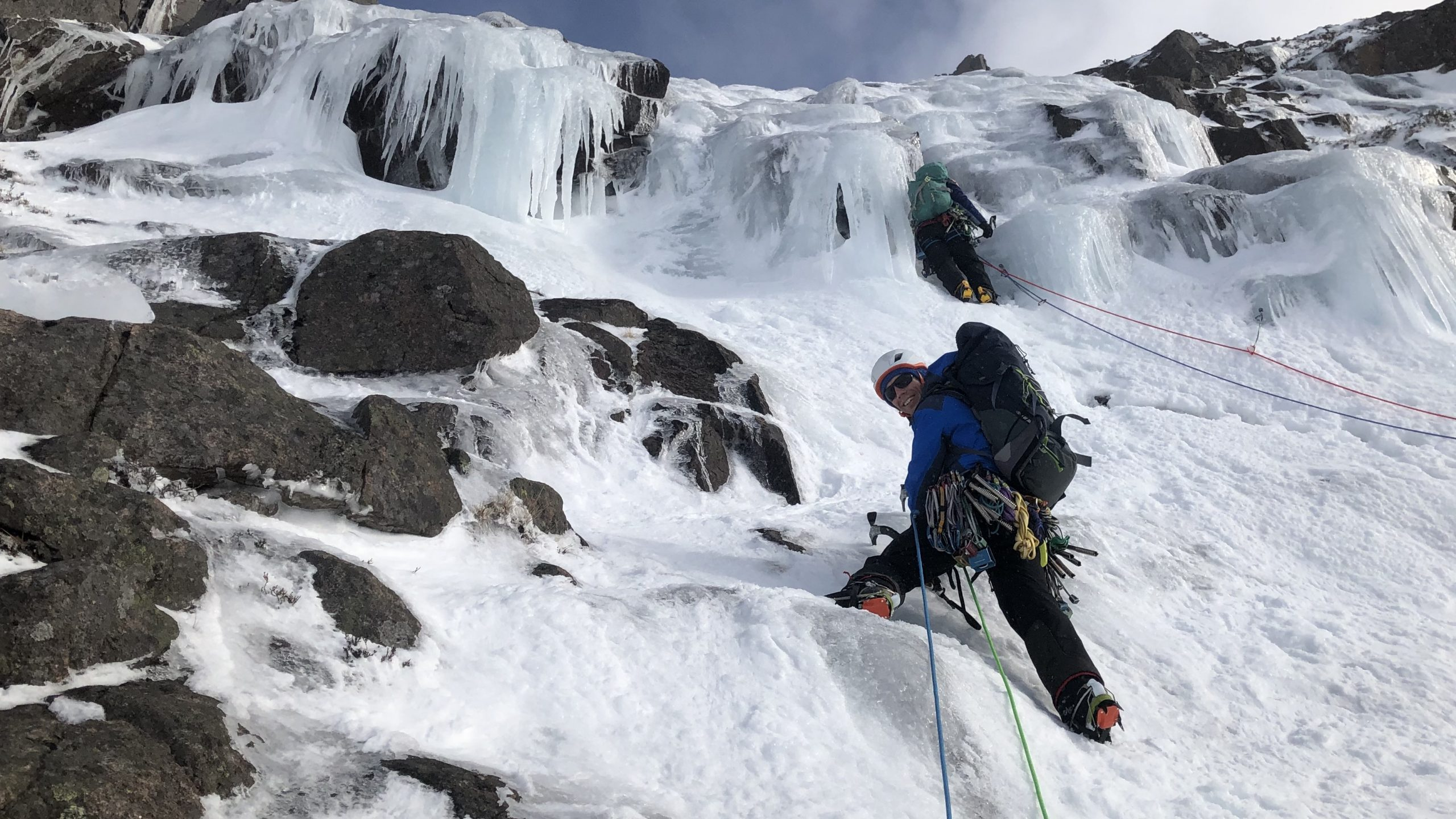 A climber leading up a steep ice climb in Lurchers Gully in the Cairngorms