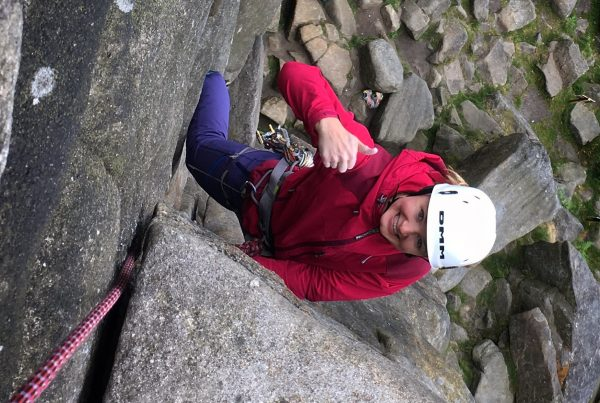 A happy climber gives the 'thumbs up' on a rock climb at Stanage Edge during a rock climbing course in the Peak District