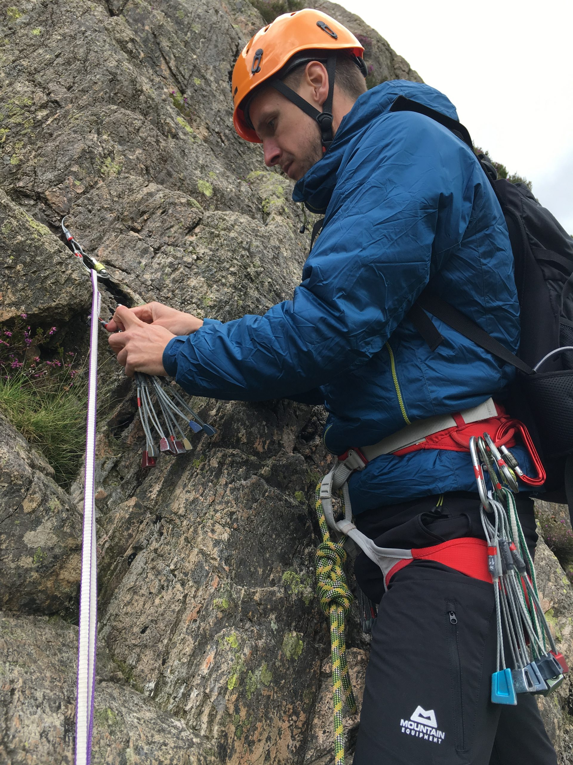 A climber selects the correct wire as protection during a learn to lead rock climbing course in the Lake District