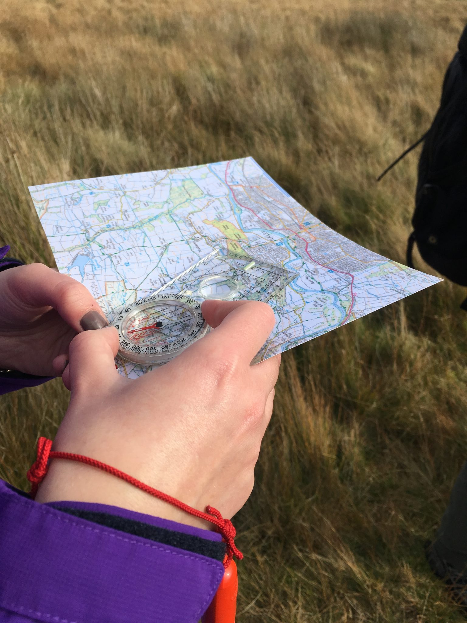 A student takes a bearing on a Silver NNAS course in the Yorkshire Dales.
