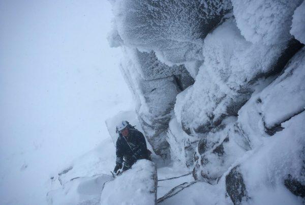 A climber battles his way through deep snow in Hidden Chimney in the Cairngorms during a winter climbing course
