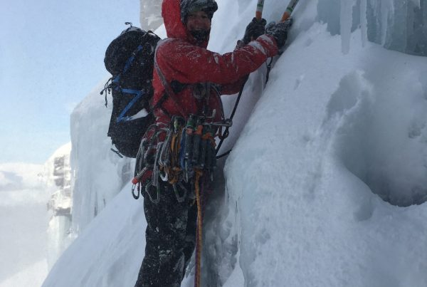 A climber battles spindrift to set off on the second pitch of Quartzvein Scoop