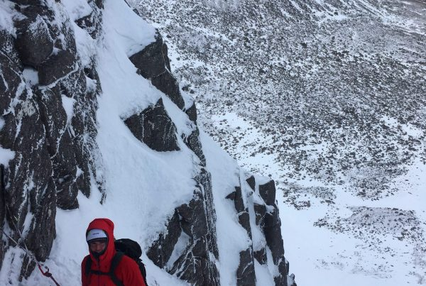 A climber waits at the belay stance of The Runnel in the Cairngorms during a winter climbing course
