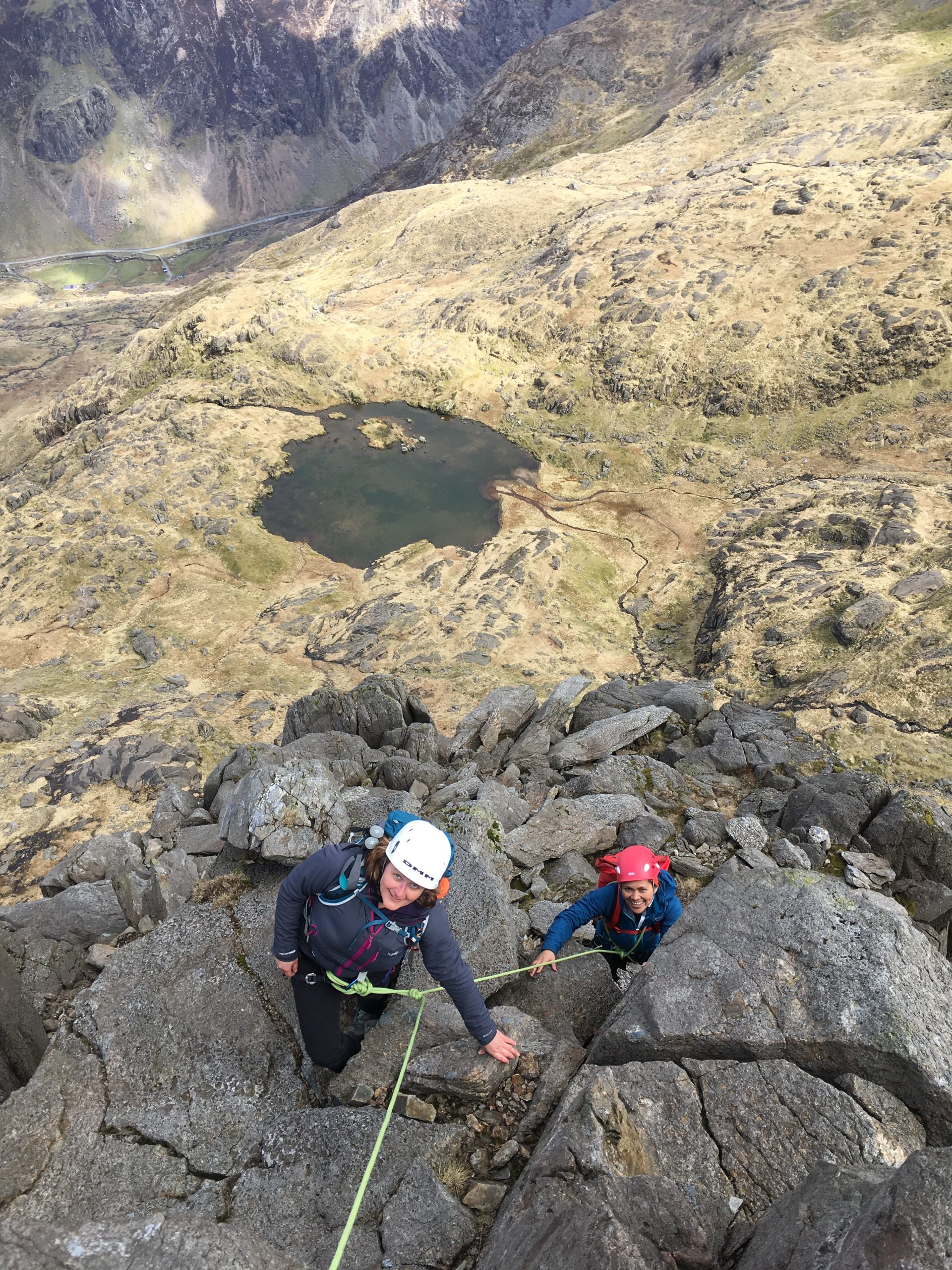 """Two climbers on the Clogwyn y Person Arete on Snowdon with Llanberis Pass below during a scrambling course in Snowdonia"""" width="""