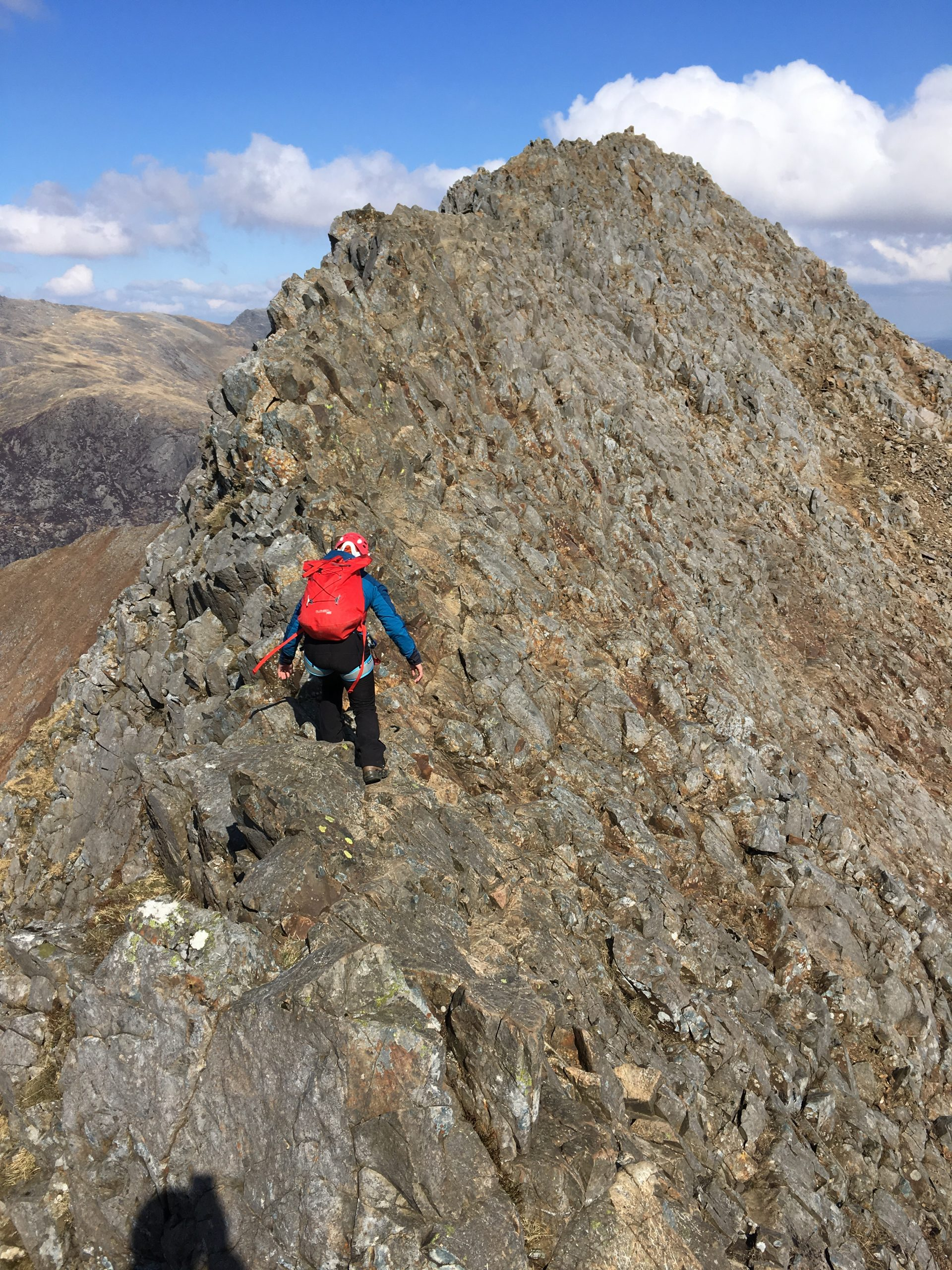 """A scrambler on a traverse of the Crib Goch ridge with the summit of Snowdon in the background during a scrambling course in Snowdonia"""" width="""