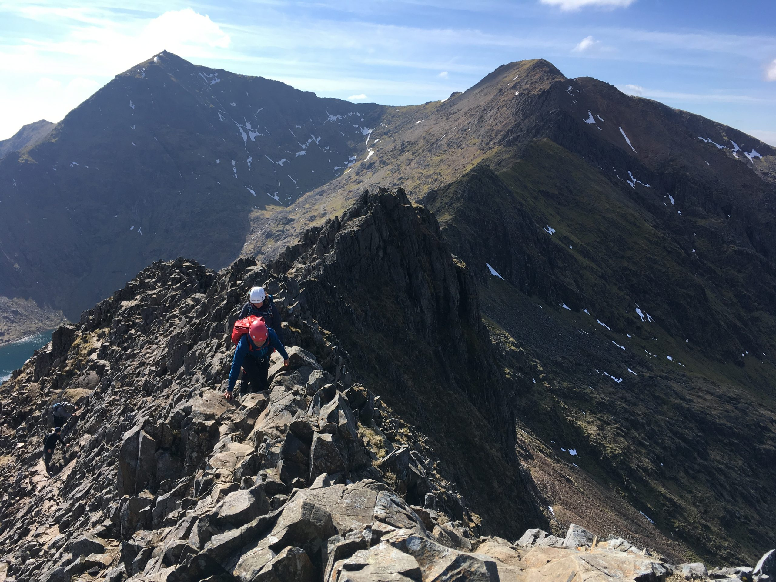 """Two scramblers on a traverse of the Crib Goch ridge with the summit of Snowdon in the background during a scrambling course in Snowdonia"""" width="""