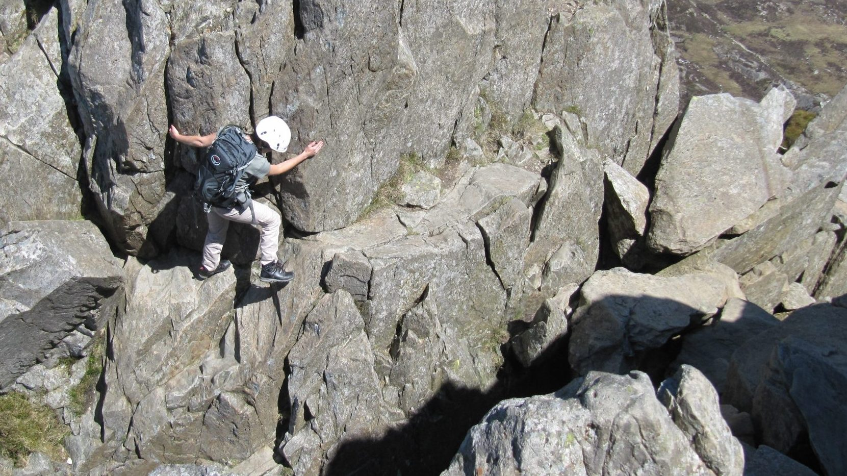 A scrambler descends cautiously into The Notch on the North Ridge of Tryfan during a scrambling course