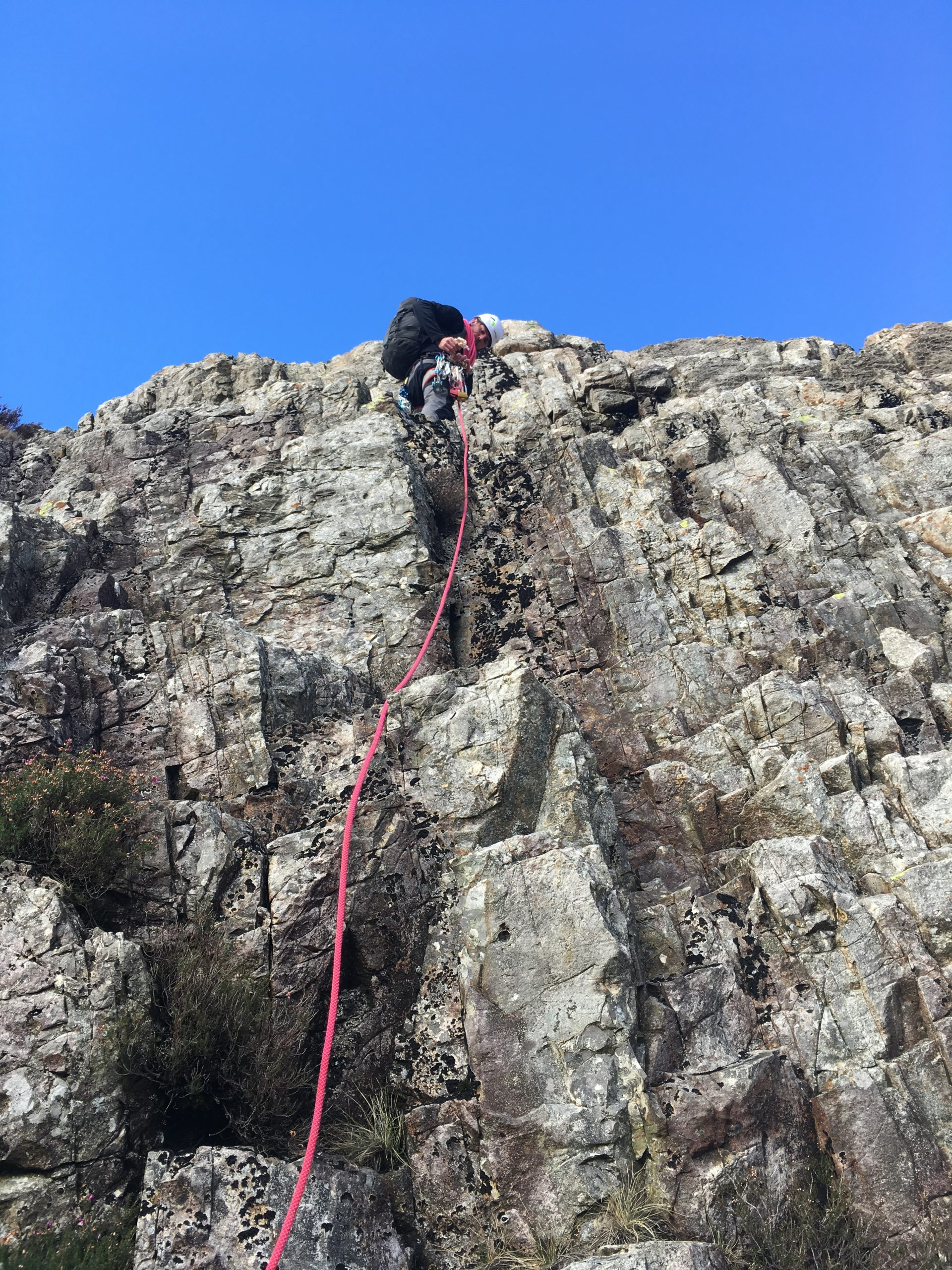 A mountaineer looks down from high up on a rock face while he learns to lead scrambles using a rope on this scrambling course in the Lake District