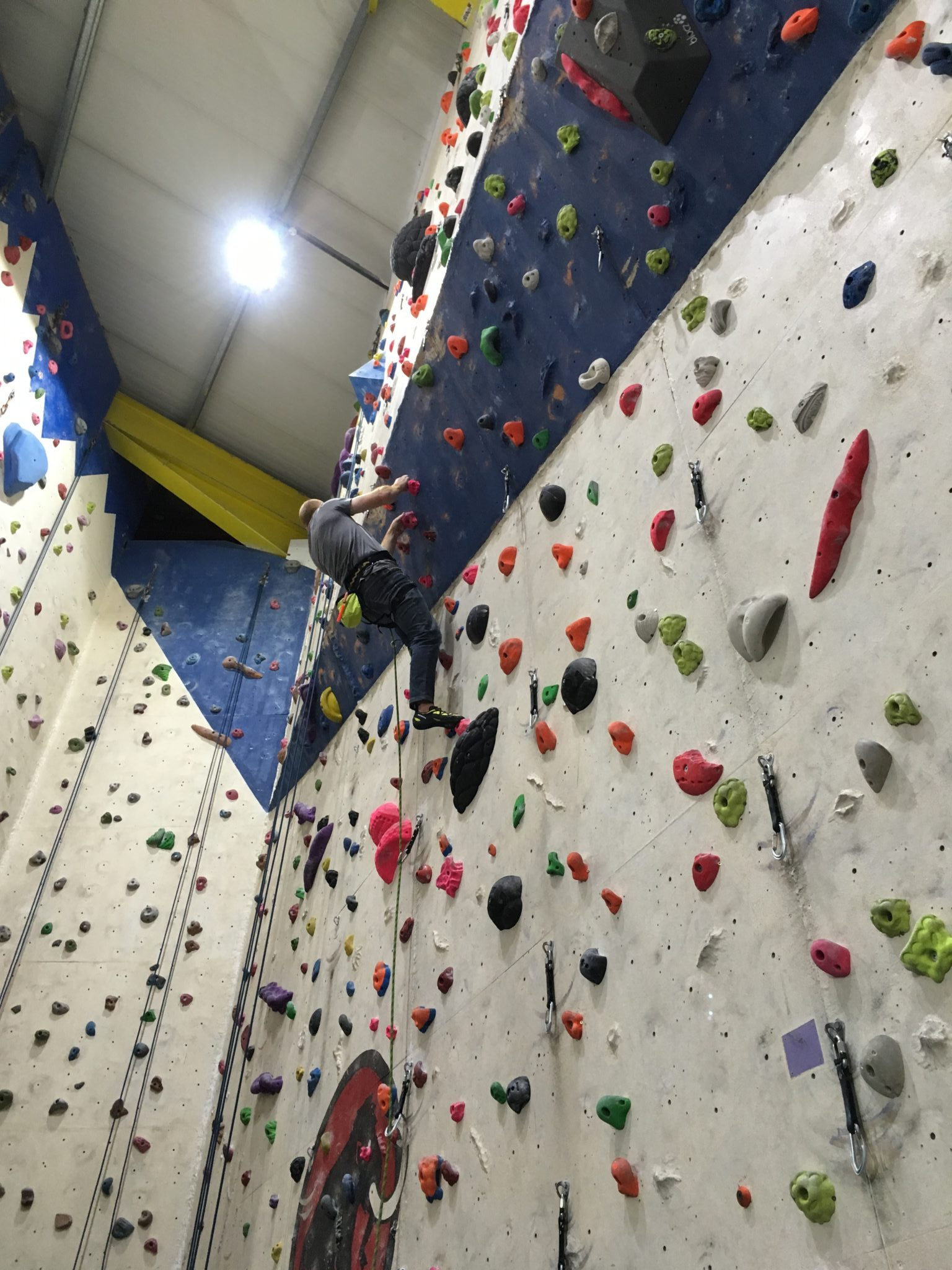 A climber leads through an overhang, as you can learn our learn to lead climbing course in Leeds