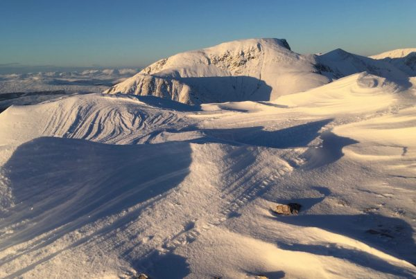 View of Ben Nevis in winter from the Mamores, with wind-carved sastrugi in the foreground
