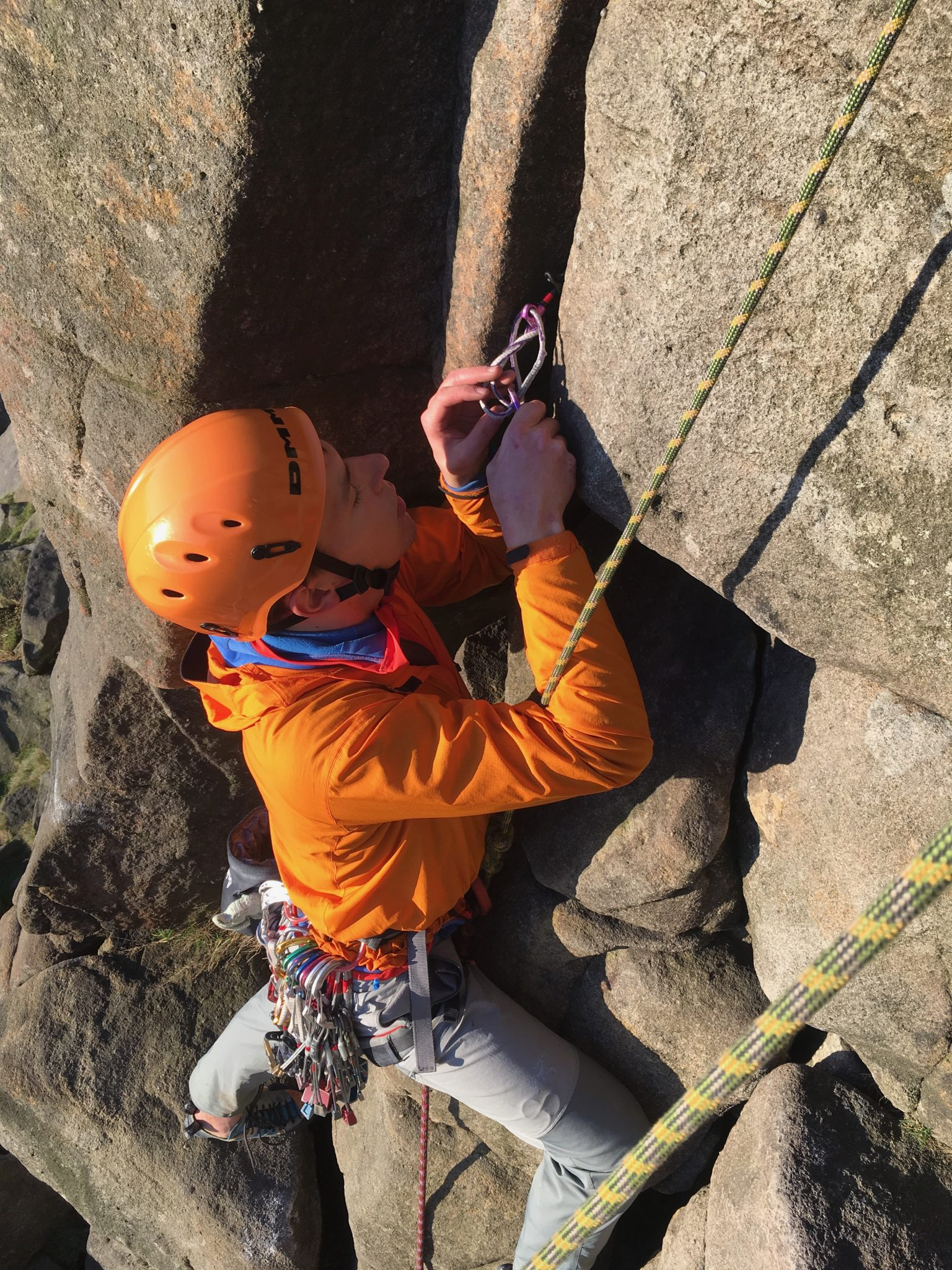 A rock climber removes equipment during a rock climbing course in the Peak District