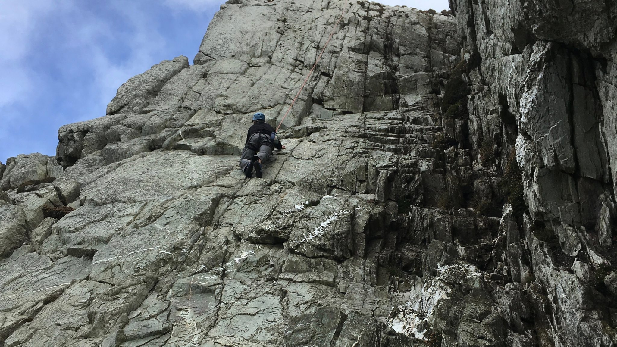 A rock climber considering his next move on our Improvers' Rock Climbing Course in Snowdonia