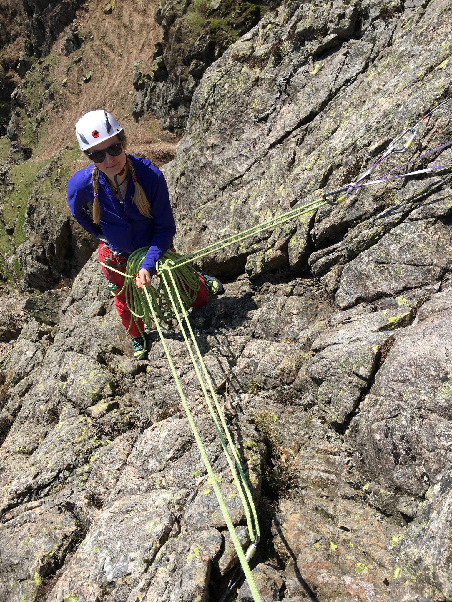 A rock climber securely anchored to the rock at her belay on a multi-pitch rock climbing course in the Lake District
