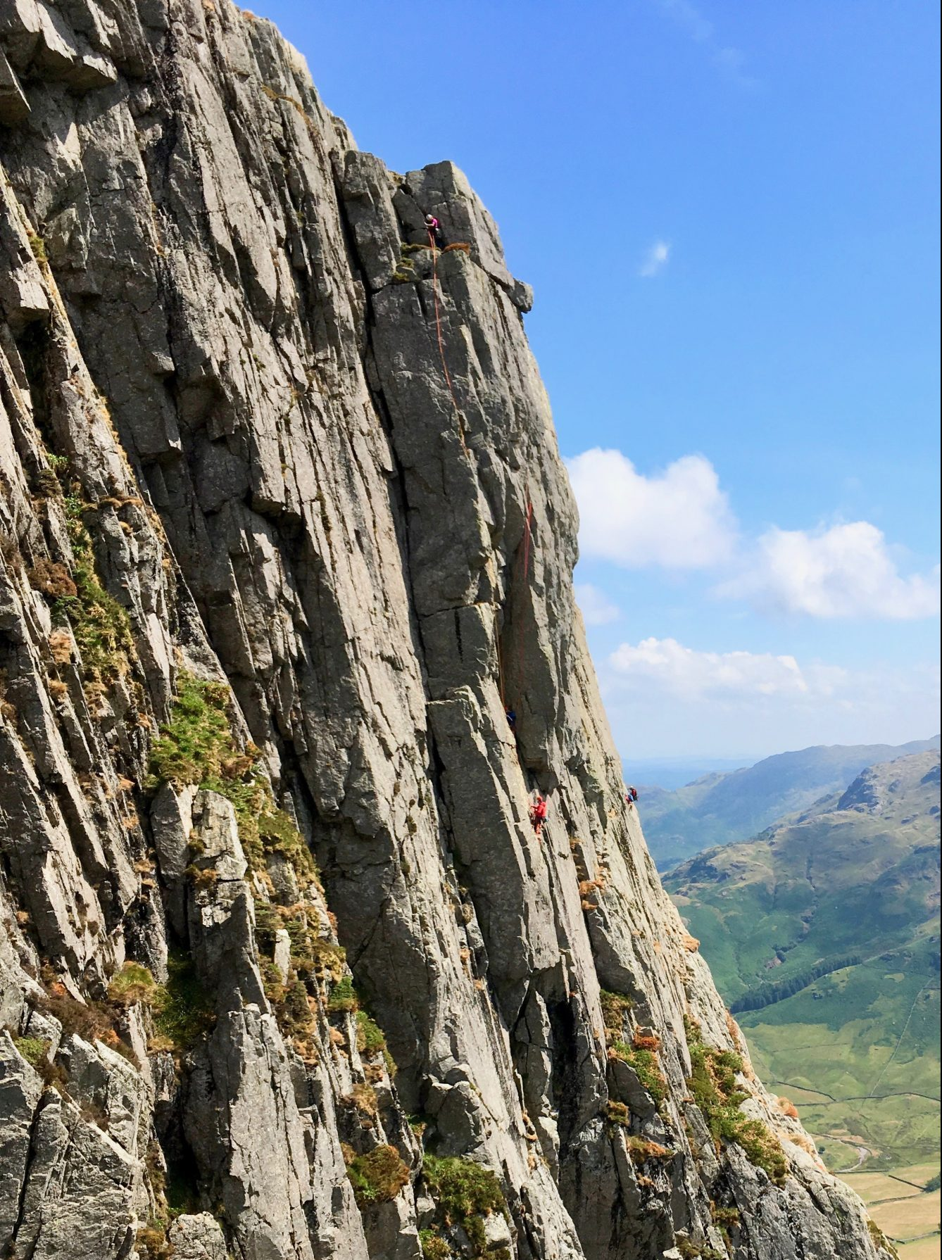 Gimmer Crag, in Great Langdale, with lots of pairs of climbers enjoying a multi-pitch rock climbing course as can be done in the Lake District and Snowdonia