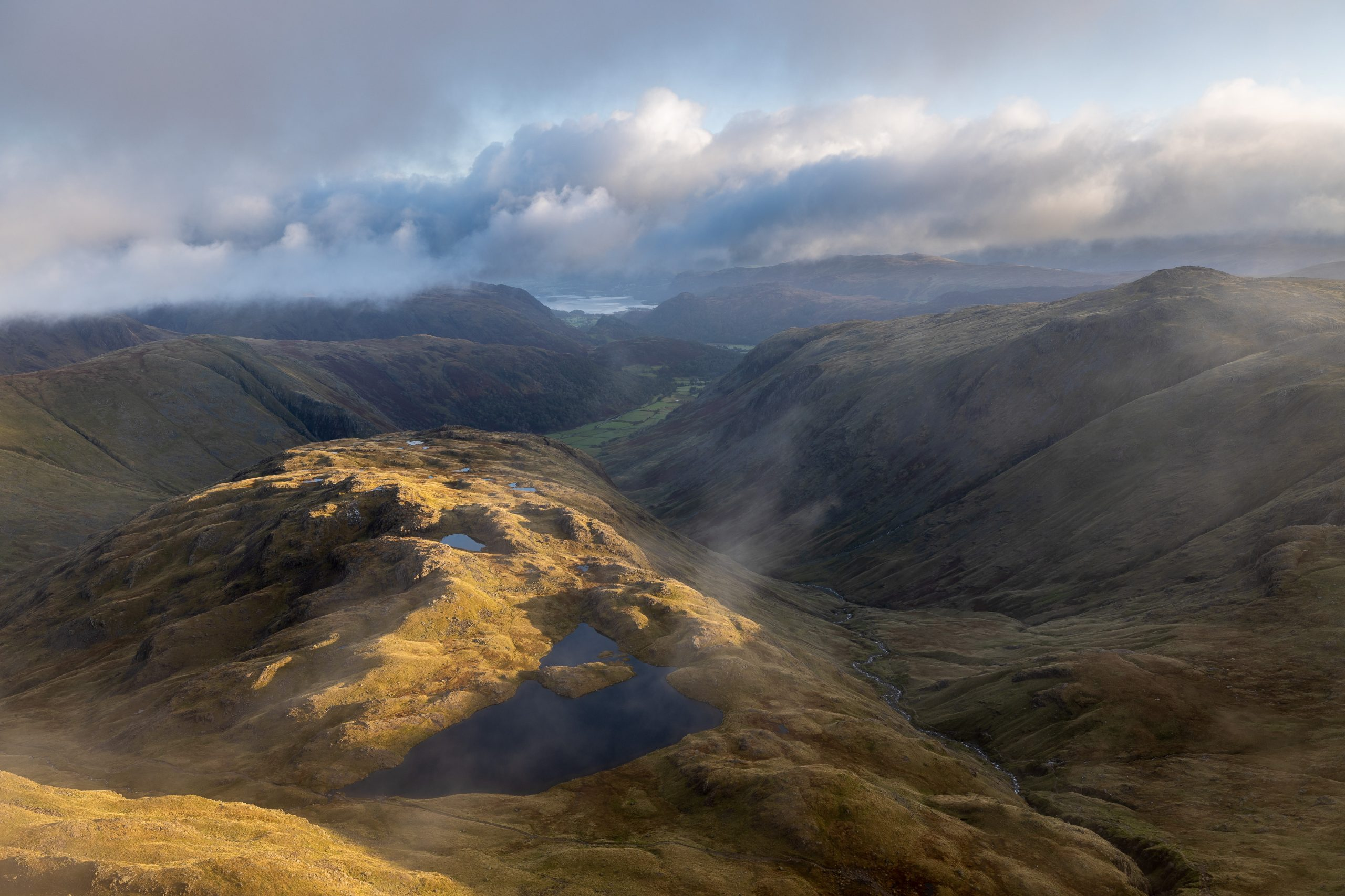 An early morning view during a guided walk on Great End in the Lake District looking down at Sprinkling Tarn and Borrowdale to Derwent Water