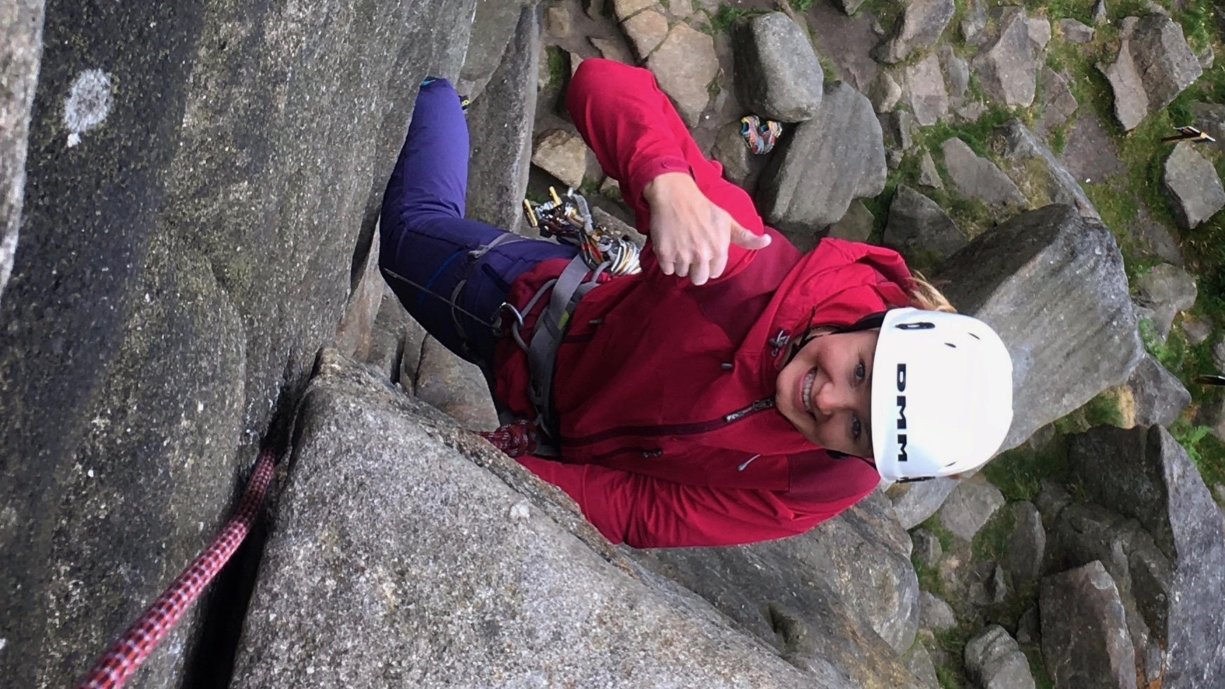 A lady smiles and gives the thumbs up while climbing at Stanage Edge on a rock climbing course.