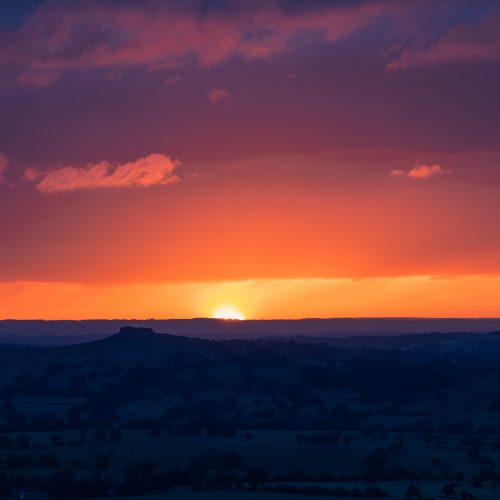 Sunrise over Almscliff Crag, Yorkshire- the sun just breaking the horizon and the sky deep orange, leaving Almscliff as a dark silhouette