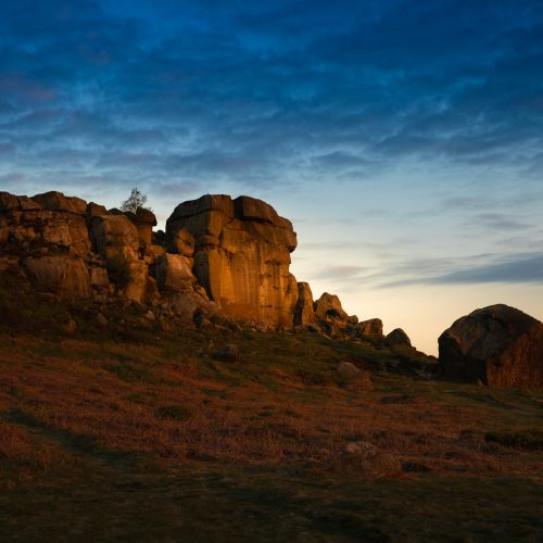 The first rays of the sun's light shining directly on the main face of the Cow and Calf Rocks, Ilkley