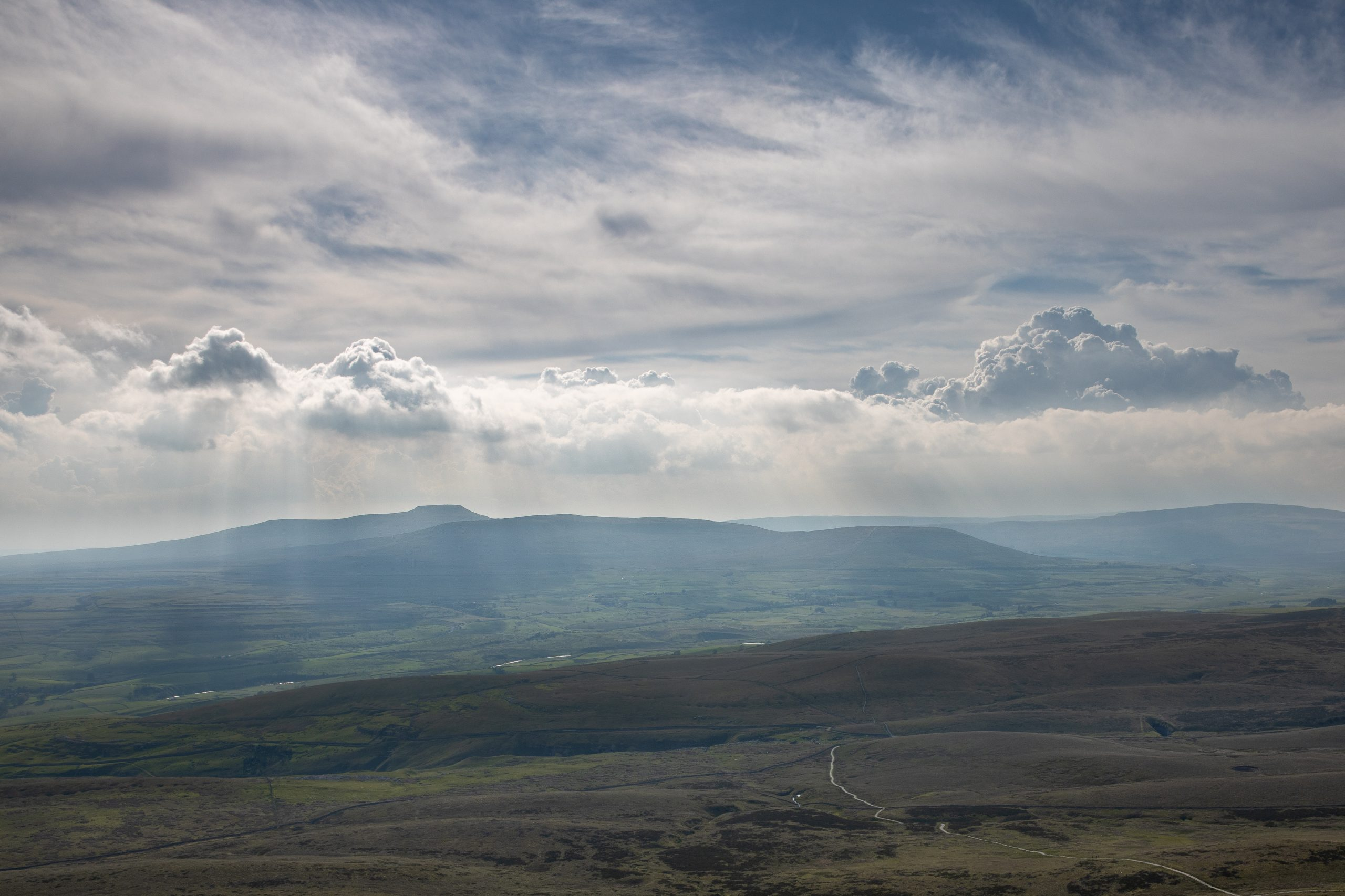 A dramatic view across the Yorkshire Dales from pen y Ghent to Ingleborough with light breaking through some storm clouds