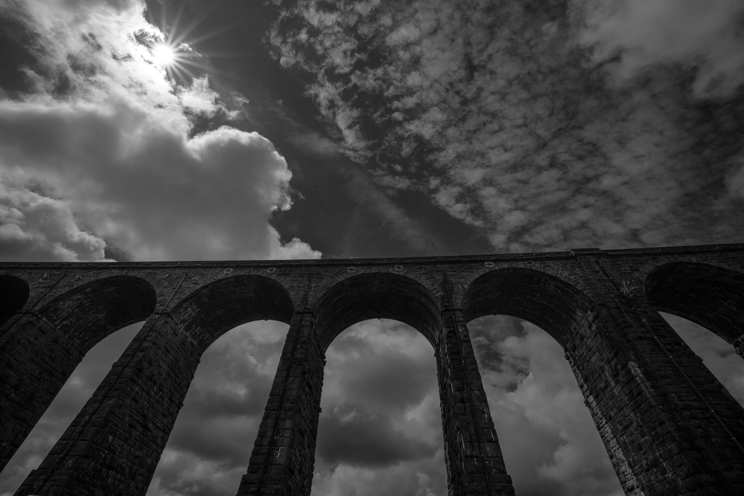 Seen in black and white, the huge arches of the Ribblehead Viaduct tower above and the sun is making a starburst pattern, during this Yorkshire Three Peaks Challenge guided walk