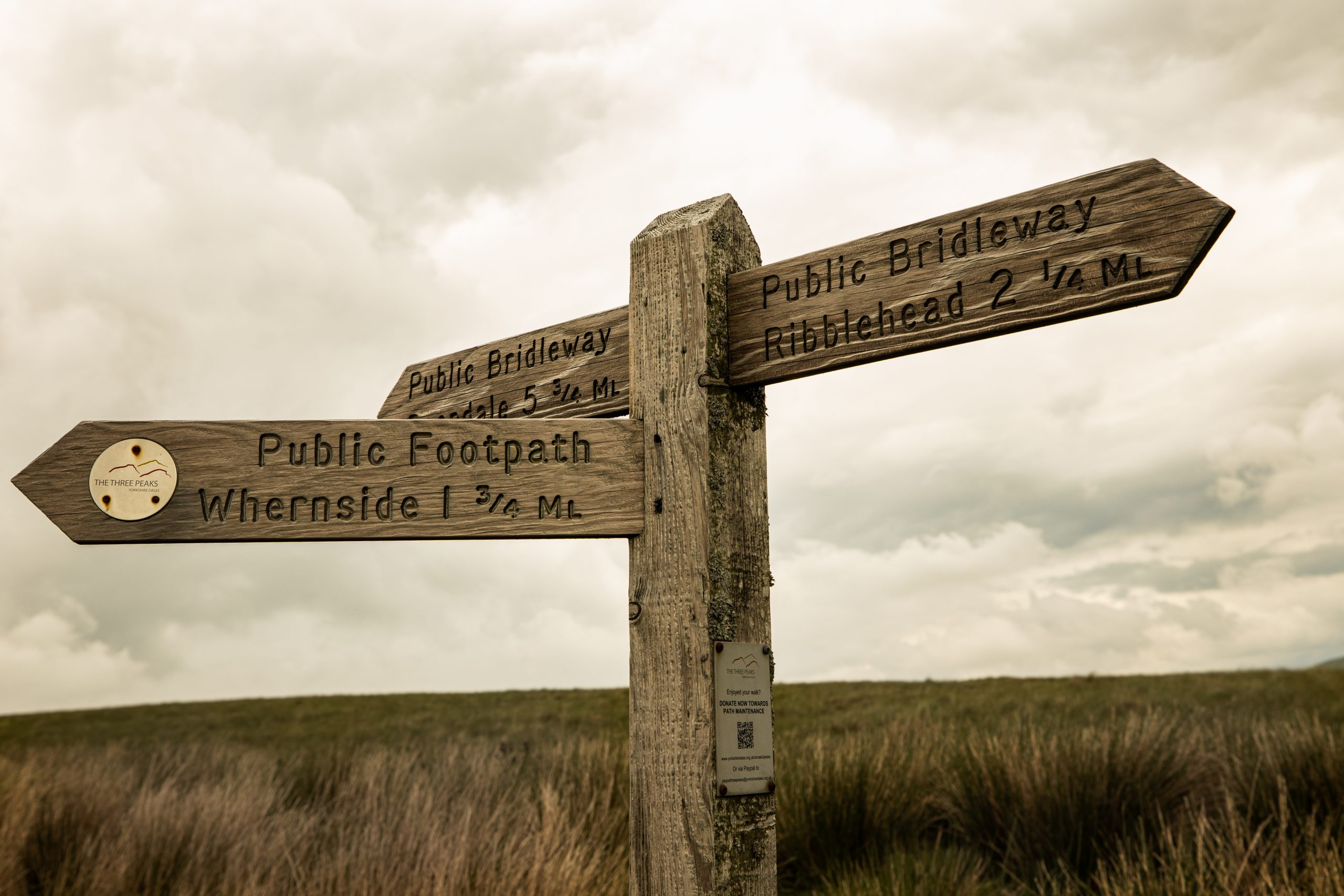 A wooden signpost indicating three different paths - one towards Ribblehead, one to Whernside and one to Dentdale, while out on a guided walk in the Yorkshire Dales