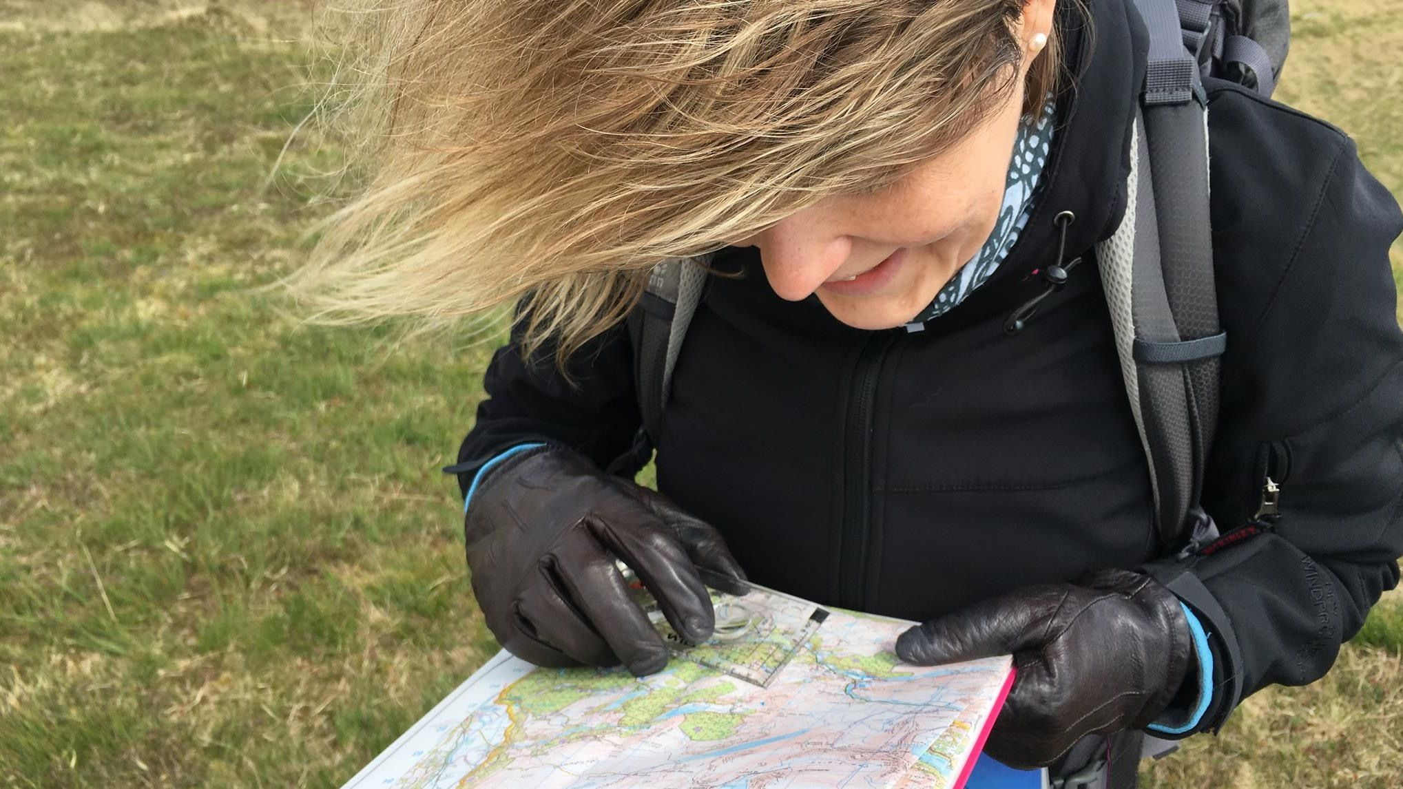 A student checks their map and compass on a beginners' navigation course