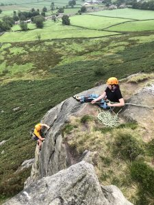 A rock climber is belayed securely at the top of Eastby Buttress as the second reaches the top during a trad lead climbing course in Yorkshire