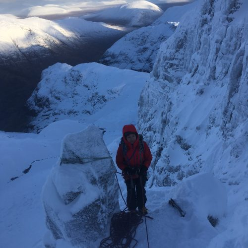 A climber on a winter mountaineering course waits at the belay on Dorsal Arete on a bitterly cold day