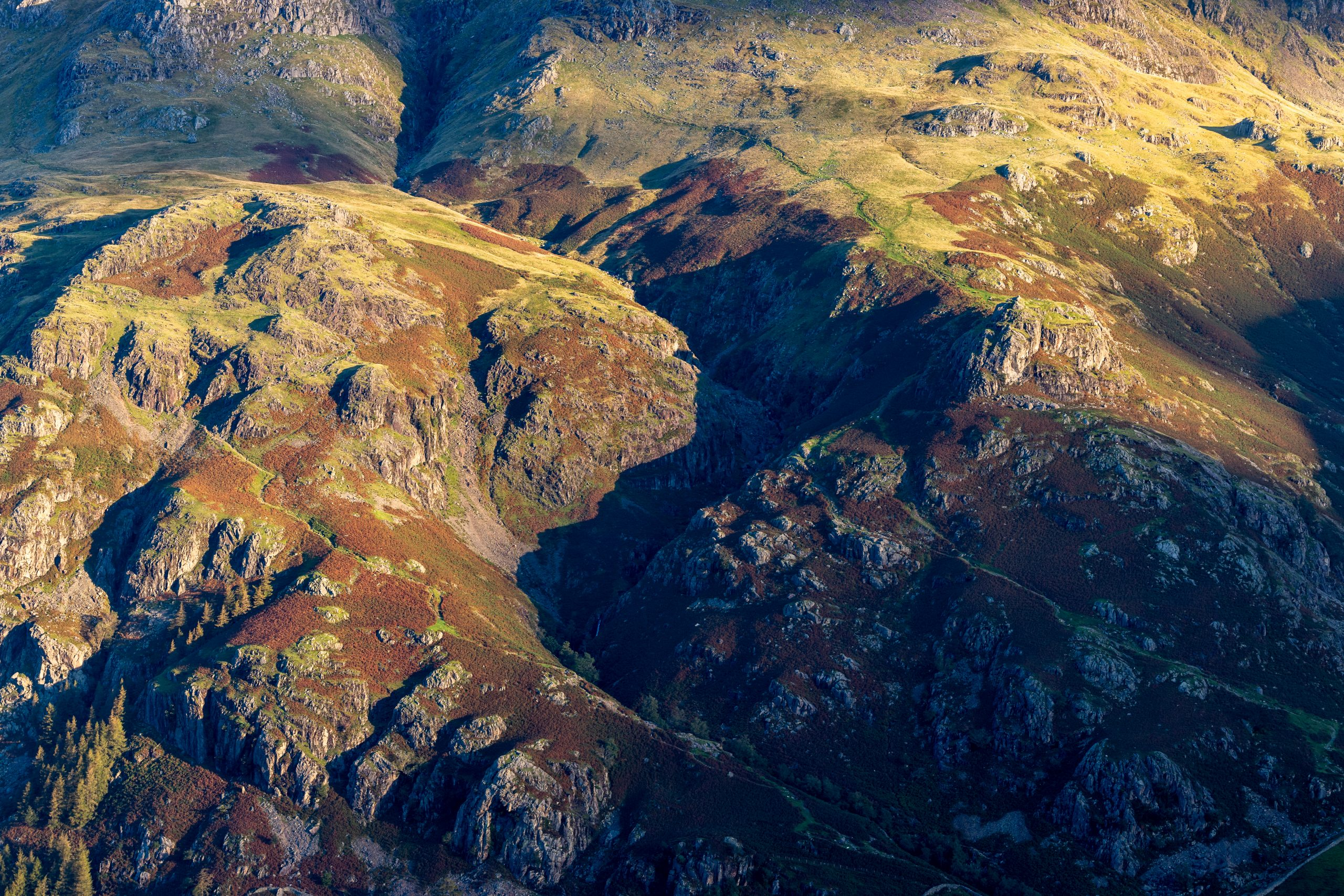 A close up of the line of Dungeon Ghyll in the Langdale Pikes in the Lake District seen in the early morning sunlight