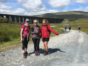 A group of walkers pose in front of the Ribblehead Viaduct during a guided walk of the Yorkshire Three Peaks