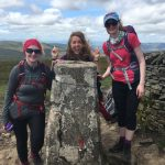 Three walkers smiling having reached the summit of Whernside on a guided walk of the Yorkshire Three Peaks