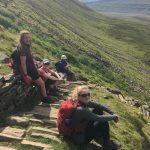A group of walkers having a short break on the steep ascent path up to Ingleborough on the Yorkshire Three Peaks challenge
