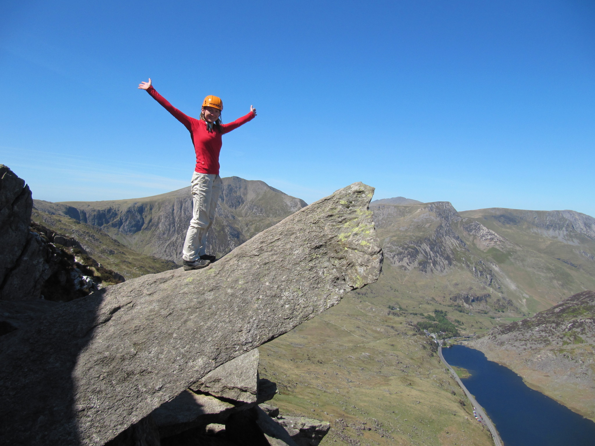 A scrambler stands confidently arms-outstretched on The Cannon on the North Ridge of Tryfan during a scrambling course