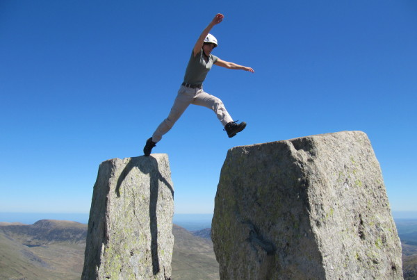 A scrambler takes the enormous step across the gap between Adam and Eve on the summit of Tryfan