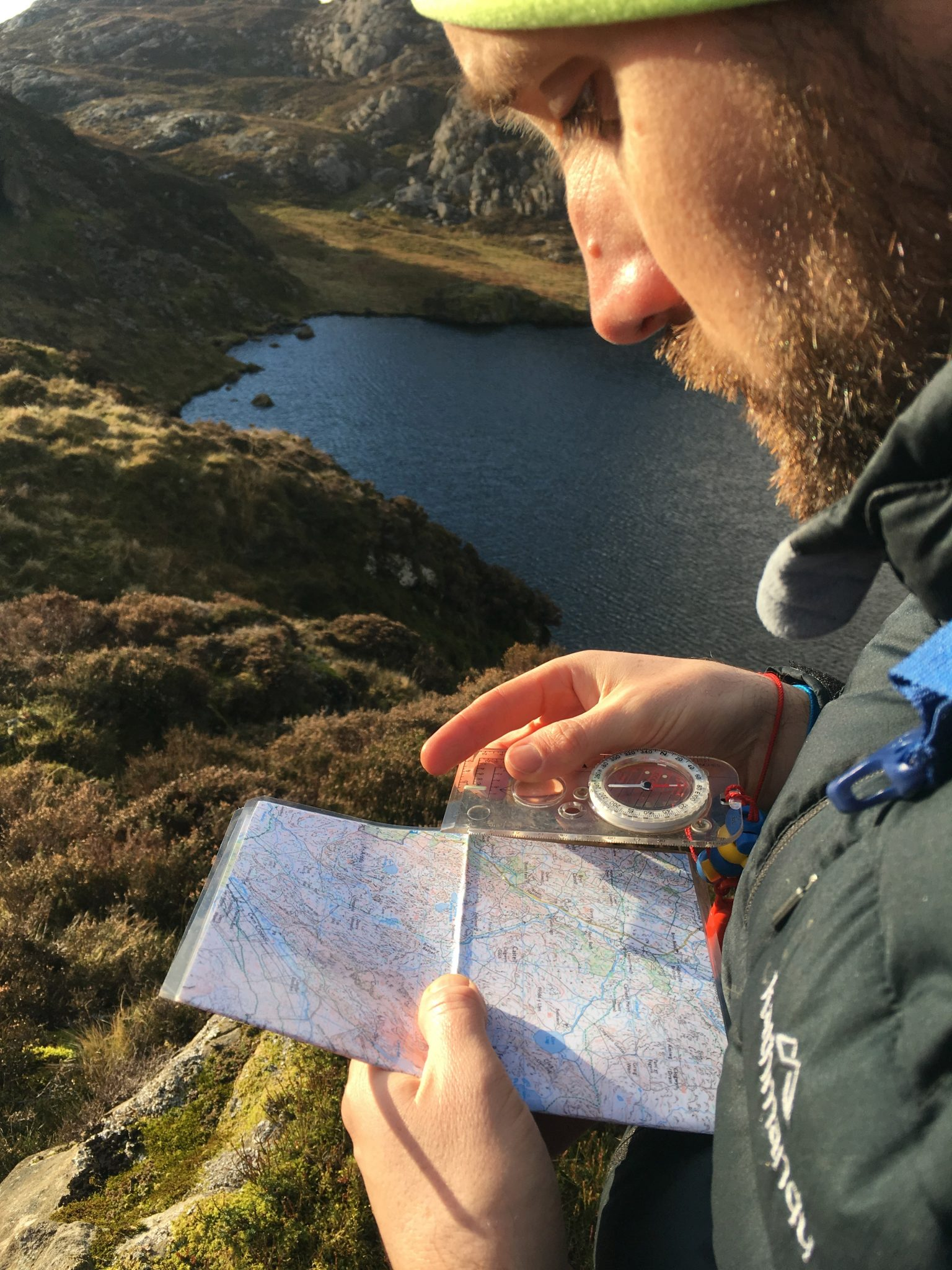 A student takes a compass bearing from a map during a mountain navigation course in Snowdonia