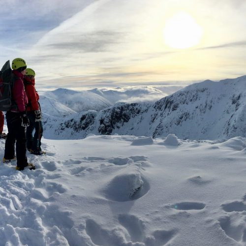A group of climbers enjoy the view of Bidean nam Bian in Glencoe from the top of Stob Coire nan Lochain on a fine winter's day