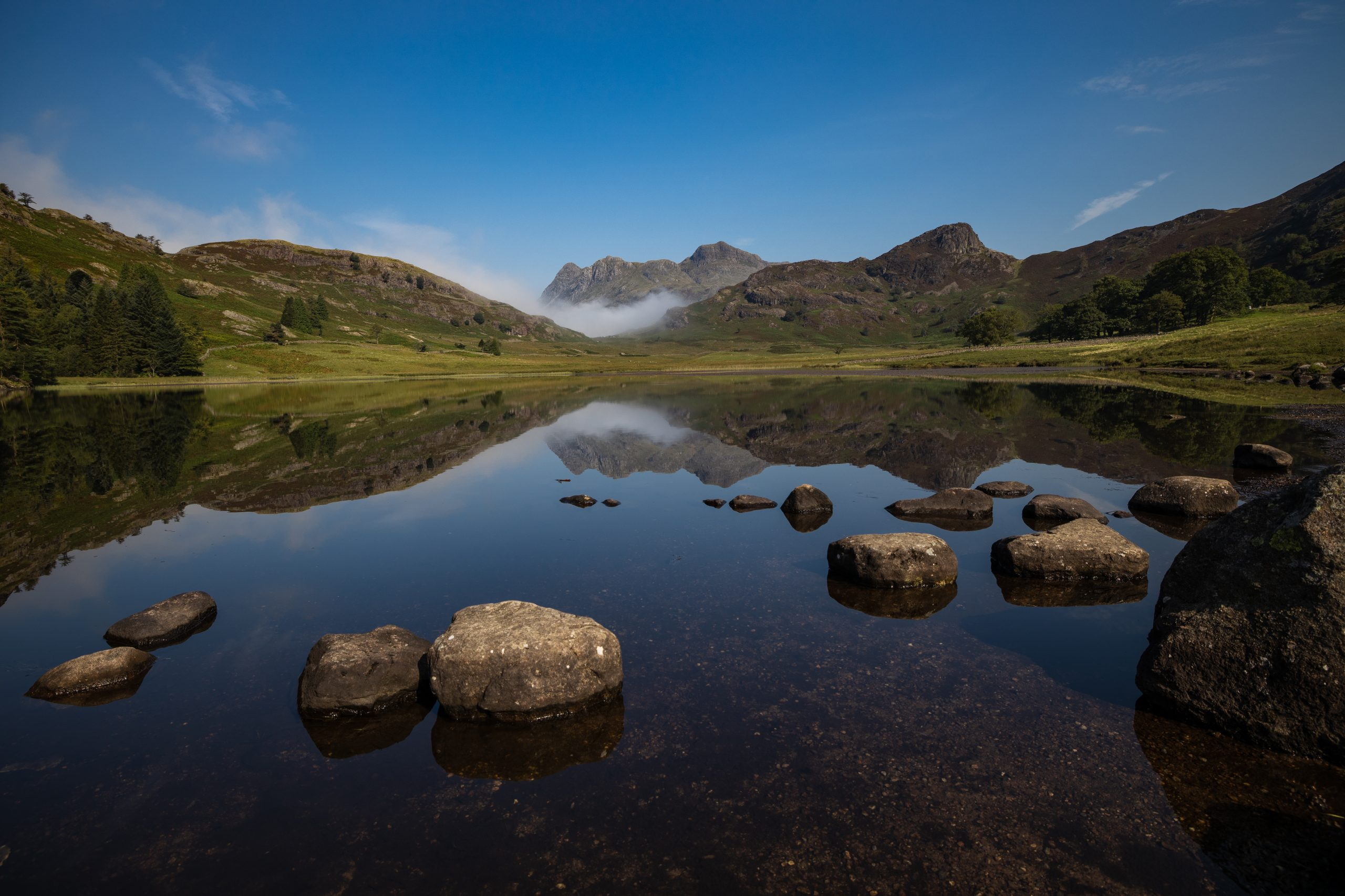 The Langdale Pikes reflected in Blea Tarn in the Lake District
