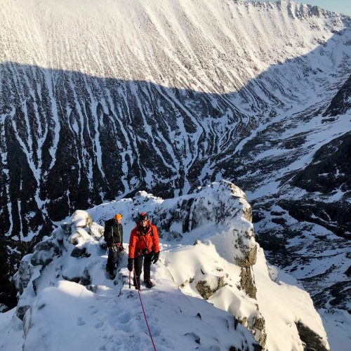 Two climbers are caught in a patch of sunlight as they make their way up Ledge Route, on Ben Nevis, which is covered in deep snow