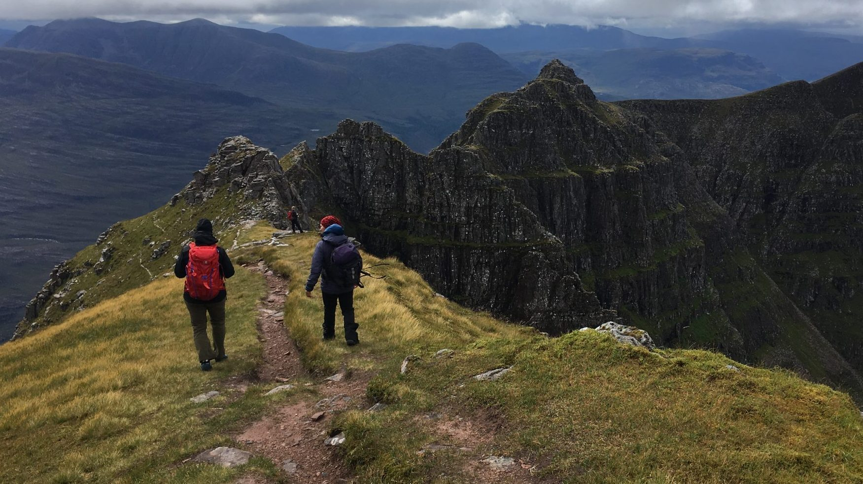 Two mountaineers approaching the narrow rocky ridge of Liathach on a summer mountaineering course