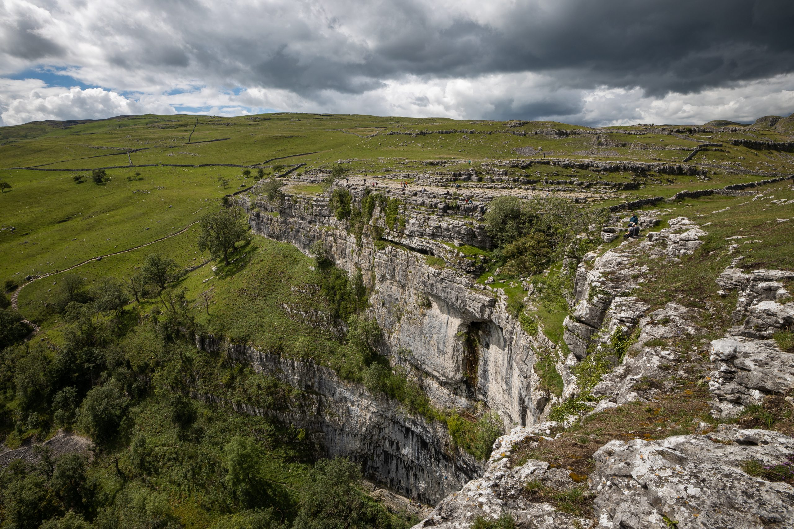 The dramatic sweep of the limestone cliffs of Malham Cove, viewed from the top on a guided walk